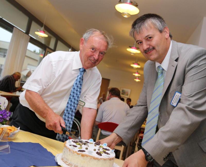Geschäftsführer Bernhard Feige (rechts) und Heinrich Niebling, ehrenamtlicher Vorstand des Diakonissenrings, schnitten die Jubiläumstorte an, während im Haus gefeiert wurde. Fotos: Thomas Kiehl